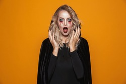 Scary woman wearing black costume and halloween makeup looking at the camera isolated over yellow background
