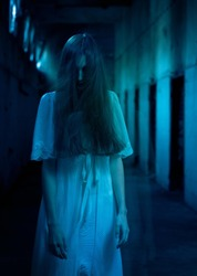 Scary woman with hair over her face standing in a dark hallway.