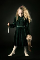 Scary young girl with a knife in a dark background