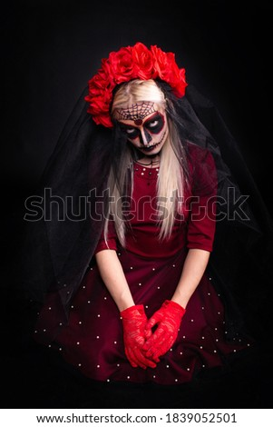 Scary young woman wearing sugar skull makeup and rose headpiece; concept of Halloween or Día de Muertos (Day of the Dead) celebration; isolated on black background Foto d'archivio ©