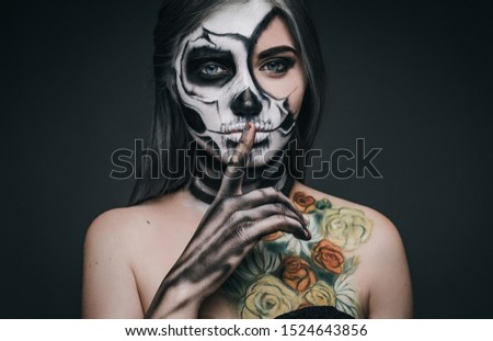 Scary young woman with skeleton makeup and painted roses keeping finger near lips and asking to keep secret during Halloween party against gray background