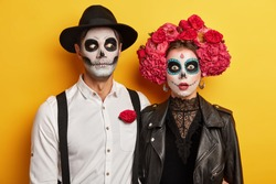 Scarying undead couple celebrate mexican holiday to remember dead relatives, dressed in carnival costume, wears skull makeup, red flowers as symbol of this event. Zombies stand indoor over yellow wall