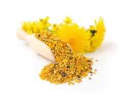 Scattered bee pollen or perga isolated on white background. Raw brown, yellow, orange and blue flower pollen grains or bee bread in wooden scoop. Healthy food supplement