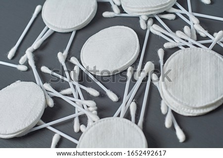 Scattered clean cotton pads and sticks lies on dark concrete desk. Close-up