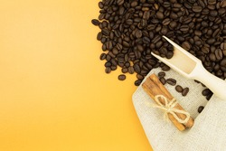 Scattered coffee beans on a yellow background. Frame for text made from coffee beans scattered on the surface of the table