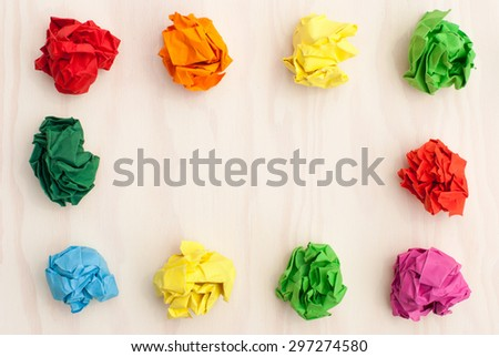 Scattered colorful crumpled paper. Colored paper balls isolated on wooden background