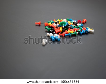 Scattered colorful push pins on a dark slate background. School and office supplies.  Zdjęcia stock ©
