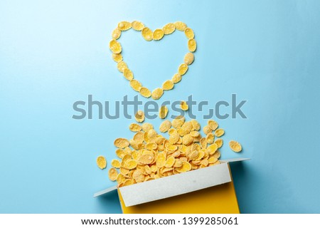 Scattered cornflakes out of box a heart shaped. Dry cereal breakfast. I love cereal #1399285061