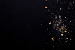 Scattered crumbs isolated on black background.