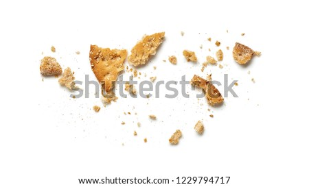 Scattered crumbs of cookie or cracker isolated on white background. Top view.