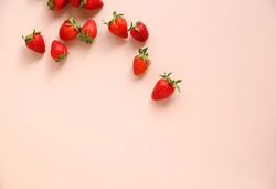 Scattered fresh strawberries on a pink background. Free space.