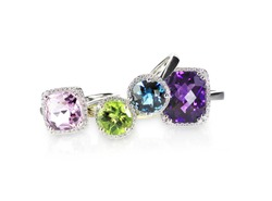 Scattered gemstone and diamond halo fine jewelry rings in a grouping