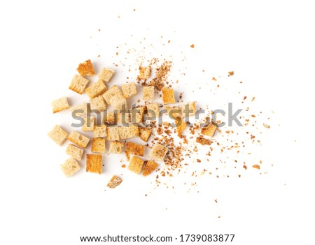 Scattered homemade bread croutons with crumbs isolated on white background top view. Crispy bread cubes, dry crumbs, rusks, crouoton or white roasted crackers cube heap