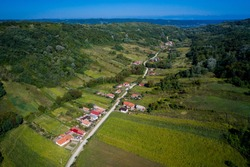 Scattered houses along a dirt road, between two hills. Aerial view