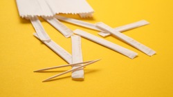 Scattered individual paper wrapped toothpicks. Wooden toothpicks in white package on yellow background