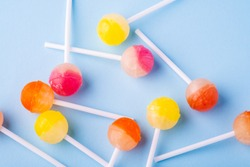 Scattered lollipop candies on blue background top view