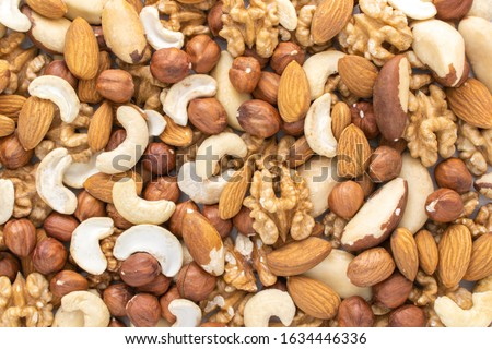 Scattered nuts on the table. Nuts background. Hazlenuts, walnuts, almond, brazilian and cashew nuts. Stock photo