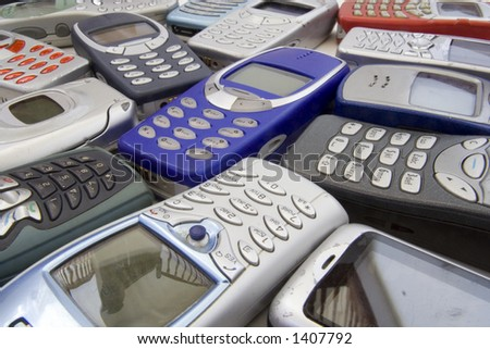 Scattered old mobile phone handsets. All makes and models in various states of disrepair.