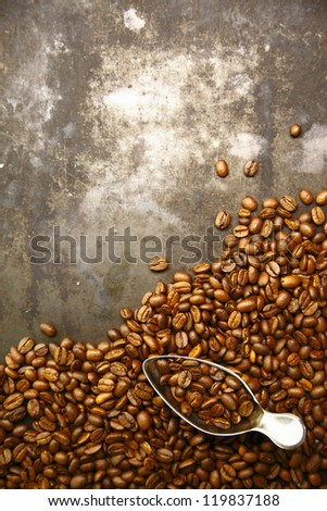 Scattered pile of aromatic fresh roasted coffee beans with a small metal scoop on a grunge background with copyspace