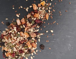 Scattered pile of chopped dried fruit and edible seeds (linseed, sunflower, pumpkin, apricots, blueberries and cranberries) on  grey blue slate textured background. Healthy vegetarian lifestyle.