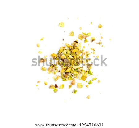 Scattered pistachio nut pieces isolated. Break chopped pistachios pile, fried baked diced pistache on white background top view