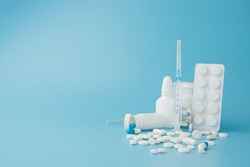 scattered variety pills, drugs, spay, bottles, thermometer, syringe and empty shopping trolley cart on blue background. pharmacy shopping concept.