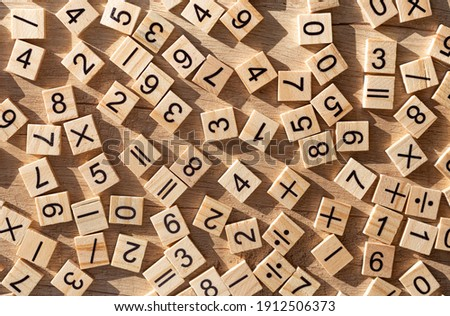 Scattered wooden plaques with numbers and signs. Flat lay. Teaching material in mathematics, Montessori method. School background. Problem solving concept. Laser cutting and printing on wood. Photo stock ©