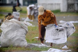 scavengers collect used newspaper waste to be recycled or sold to waste banks