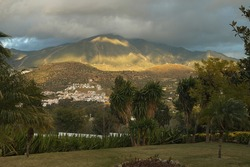 Scenary of palm trees, clouded sky with golden light on mountain side in Venuela, Andalusia, Spain