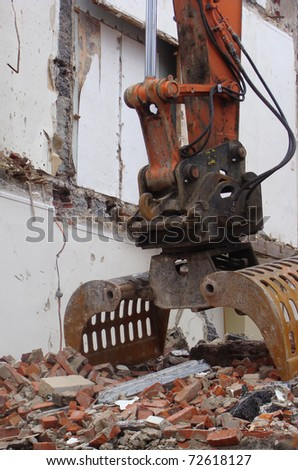 scene from a demolished house on a construction site with construction equipment