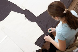 Scene in the studio for tailoring work clothes. A cutter girl works at a large table with a marker marking the fabric for further sewing of work clothes.