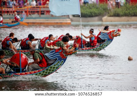 Scene of a competitive boat racing in the traditional Dragon Boat Festival in Taipei, Taiwan, with athletes pulling vigorously on their oars and competing with all their strength in colorful boats