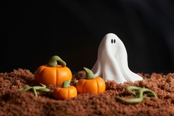 Scene of halloween, ghost and pumpkins made of sugar paste on chocolate cake ground, black background, copy space