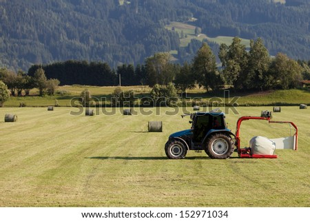 Scene of haymaking, tractor with hay cart working on the field  as agricultural background. Harvesting
