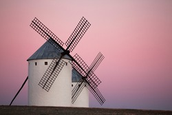 Scene with two windmill and pink sunset in Campo de Criptana in the month of March, Spain.