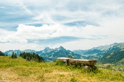 Scenery alpine panorama of Switzerland in sunny day with view on mountains, green forest, meadow, blue sky and white clouds and with a bench for rest in the foreground
