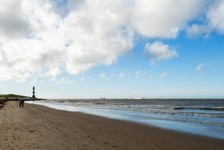 Scenery at the seaside with lighthouse and passing ships in Breskens, Netherlands