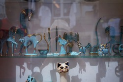 Scenery blue porcelain cats and owls with golden elements on a showcase behind glass