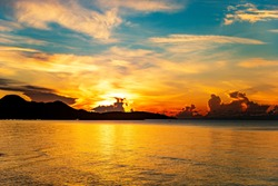 Scenery morning view of sunrise at the horizon, sunlight shines through the clouds and mountain into the sea and coast. The glittering golden yellow reflection against the sea make it feel refreshed.
