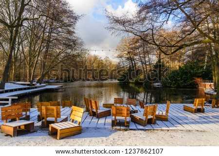 Scenery of frozen lake, snow cover wooden outdoor chairs, seats and deck waterside and forest in winter atmosphere. View from Café am Neuen See inside Tiergarten park in Berlin with sunset light.