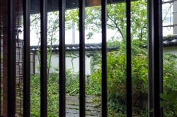scenery of japanese garden seen through latticed window of japanese restaurant in chikuma city, nagano prefecture, japan