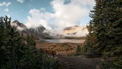 Scenery of Mount Assiniboine with lake magog in autumn forest and wooden bench at viewpoint. British Columbia, Canada