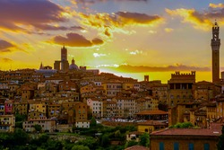 Scenery of Siena at sunset, a beautiful medieval town on a hilltop in Tuscany Italy, with view of architectural landmarks, Mangia Tower, Duomo Dome & Bell Tower bathed in golden sunlight