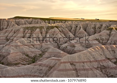 Scenery of South Dakotas Badlands National Park. Eroded Sandstones Landscape and Badlands Loop Road with Two Travel Trailers on the Road. Summer Time Badlands Panorama. Nature Photo Collection