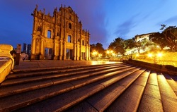 Scenery of the Ruins of St. Paul's Church in the Historic Center of Macau, China, with stone steps leading to the beautiful facade of the historic architecture & lights glistening in morning twilight