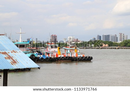 Scenery of towboats lie at the pier in the river with city landscape and cloudy sky background of rainy summer.