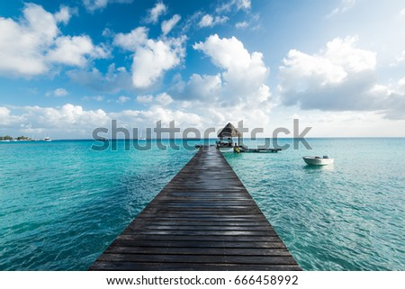 Scenery perspective view of a wooden wet pier on the tropical seashore with clear blue sky with white clouds, white boat and sea with turquoise water.
