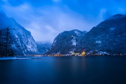 Scenery view of Austrian snowy village Hallstatt by lake surrounded by snow mountains with lights on after sunset at night time, Austria. Image contains of noise and dust from snow falling down.
