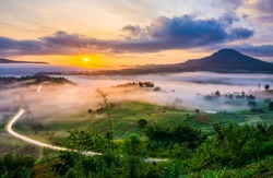 Scenery view of sunrise with mist and traffic trails from Khao Ta-Khian Ngo Viewpoint. Location in Khao Kho District, Phetchabun, Thailand, Southeast Asia.
