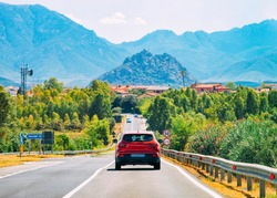 Scenery with red car on the highway in Carbonia near Cagliari in Sardinia in Italy. Nature and Automobile back in the road. Mountains and hills on the background
